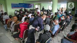 Para pedagang menunggu untuk mengikuti vaksinasi COVID-19 di Pasar Induk Kramat Jati, Jakarta Timur, Selasa (9/3/2021). Pelaksanaan vaksinasi berlangsung mulai tanggal 8 hingga 11 Maret pukul 08.00-15.00 WIB. (Liputan6.com/Faizal Fanani)