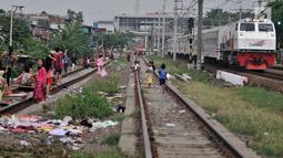 Anak-anak bermain layang-layang di rel kereta api kawasan Jakarta Timur, Kamis (3/1). Rel yang sering dilintasi kereta api tersebut sangat membahayakan diri mereka. (Merdeka.com/Iqbal Nugroho)