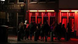 Orang-orang berjalan melewati rumah bordil di Red Light District Amsterdam, Belanda, Rabu (3/4). Pemerintah mengumumkan bakal segera mengakhiri tur wisata ke Red Light District. (REUTERS/Yves Herman)