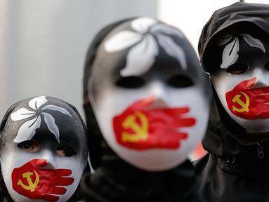 Demonstran mengenakan topeng saat berkumpul untuk menunjukkan dukungan kepada Uighur dan perjuangan mereka terhadap hak azasi manusia (HAM) di Hong Kong, Minggu (22/12/2019). Demonstran memprotes kebijakan China terkait minoritas Uighur. (AP Photo/Lee Jin-man)