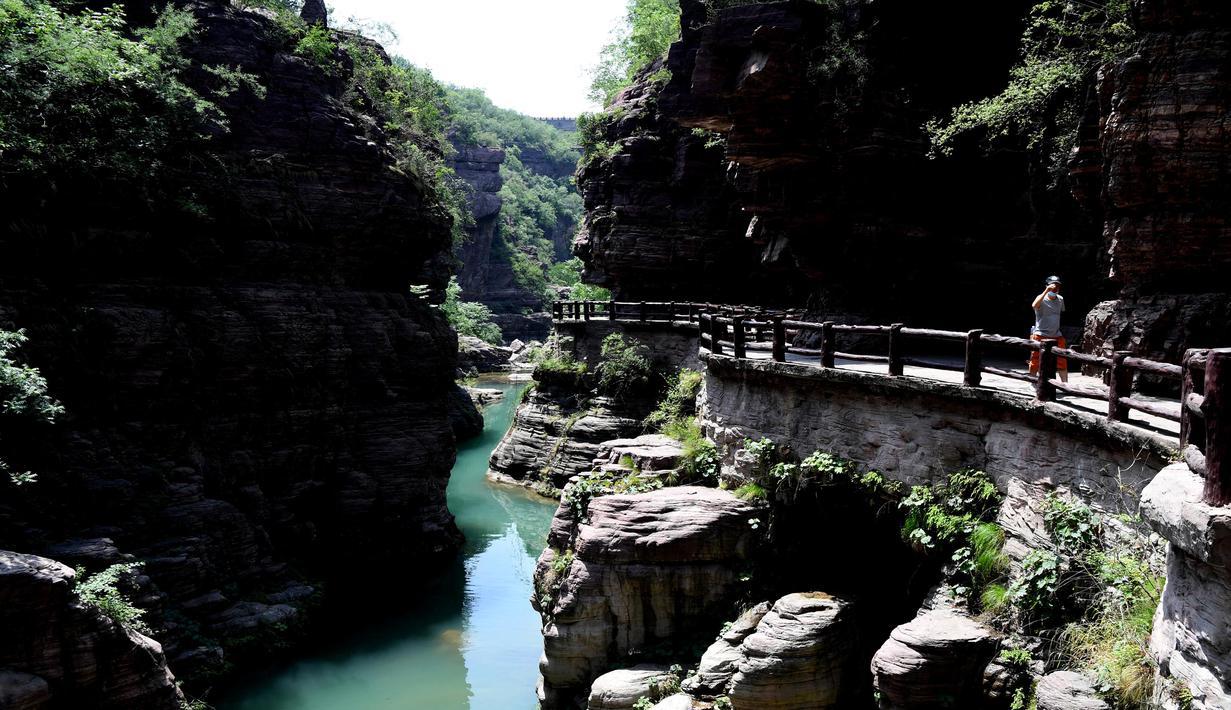 Pemandangan Ngarai Hongshi (Batu Merah) di lokasi wisata Gunung Yuntai di Wilayah Xiuwu, Provinsi Henan, China tengah (28/5/2020). Ngarai di dataran Danxia sepanjang 1,5 kilometer tersebut memiliki batu pasir berwarna kemerahan. (Xinhua/Zhu Xiang)