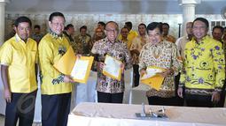 Wapres Jusuf Kalla bersama Ketum Partai Golkar versi munas Bali Aburizal Bakrie dan Ketum Partai Golkar versi munas Ancol Agung Laksono menunjukan berkas kesepakatan islah setelah menandatanganinya di Jakarta, Sabtu (30/5). (Liputan6.com/Johan Tallo)