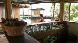 Seorang wanita menunggu di sebuah restoran di pulau buatan dari sampah plastik daur ulang di Abidjan, Pantai Gading pada Agustus 2019. Eric Becker asal Prancis membangun sebuah pulau terapung dari sekitar 700.000 sampah plastik daur ulang yang dikumpulkan di daerah sekitarnya. (ISSOUF SANOGO/AFP)