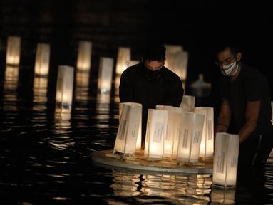 Orang-orang meletakkan lentera kertas di atas permukaan air untuk mengenang mereka yang meninggal akibat COVID-19 di Brasilia, Brasil, 30 November 2020. Brasil mencatat 21.138 kasus baru dan 287 kematian baru akibat COVID-19. (Xinhua/Lucio Tavora)