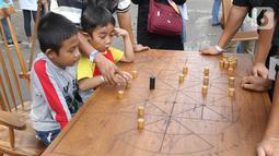 Anak-anak mengikuti permainan tradisional pada Pekan Kebudayaan Nasional di Istora Senayan, Jakarta, Sabtu (12/10/2019). Perhelatan itu dimeriahkan kompetisi olahraga tradisional berupa permainan rakyat seperti egrang, lari balok, terompah panjang, dan hadang.. (Liputan6.com/Angga Yuniar)
