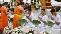 Biksu mencukur rambut anak-anak, yang diselamatkan dari gua di Thailand, pada upacara pentahbisan di Kuil Wat Phra That Doi Wao, Chiang Rai, Selasa (24/7). 11 dari 12 remaja itu menjalani ritual menjadi biksu. (Panumas Sanguanwong/THAI NEWS PIX/AFP)