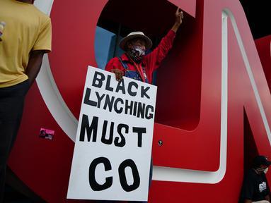 Orang-orang menggelar aksi protes di kantor pusat CNN di Atlanta, Georgia, Jumat (29/5/2020). Massa yang mengecam kematian George Floyd (46) oleh polisi melakukan vandalisme dan perusakan gedung CNN pusat. (Elijah Nouvelage/Getty Images/AFP)
