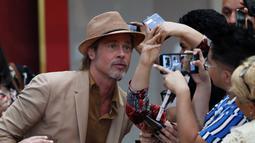"""Aktor Brad Pitt berselfie dengan penggemar saat menghadiri acara karpet merah untuk film """"Once Upon a Time In Hollywood"""" di Mexico City (12/8/2019). Film garapan sutrada Quentin Tarantino ini akan diputar di Mexico City pada Agustus 23.  (AP Photo/Marco Ugarte)"""