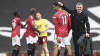 Pelatih Manchester United, Ole Gunnar Solskjaer, mengusap kepala Mason Greenwood usai laga melawan Burnley pada laga Liga Inggris di Stadion Old Trafford, Minggu (18/4/2021). MU menang 3-1 Burnley. (Gareth Copley/Pool via AP)
