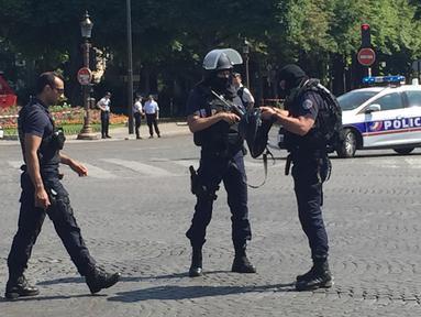 Petugas kepolisian menutup akses jalan Champs Elysees di Paris, Prancis, Senin (19/6). Seorang laki-laki yang diduga terkait dengan ekstrimis menabrakkan mobilnya ke arah mobil van polisi di jalanan ikonik itu. (AP Photo/Bertrand Combaldieu)