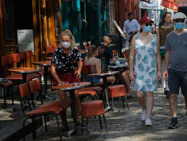 Turis berjalan-jalan di distrik Montmartre, Paris pada Senin (10/8/2020). Pemerintah Kota Paris mengumumkan masker wajib dipakai di area luar ruangan yang ramai di ibu kota Prancis itu mulai Senin (10/8) untuk mengendalikan peningkatan tingkat infeksi virus corona. (AP Photo/Michel Euler)
