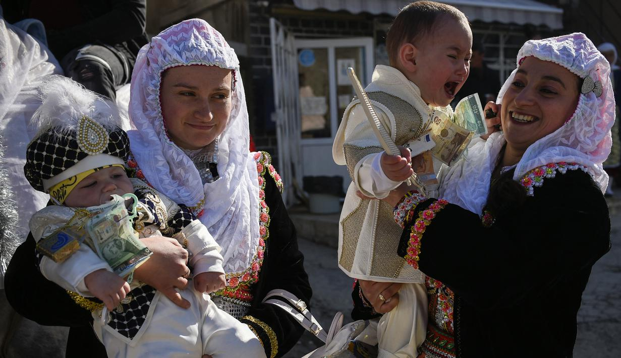 "Wanita muslim Bulgaria menggendong putra mereka selama upacara sunat massal untuk anak laki-laki di Desa Ribnovo, 11 April 2021. Penduduk Desa Ribnovo adalah muslim berbahasa Bulgaria, kadang-kadang disebut sebagai ""Pomaks"" atau ""orang yang menderita"". (Nikolay DOYCHINOV/AFP)"