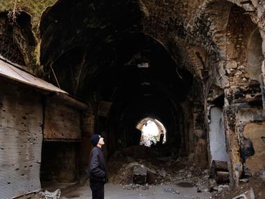 Seorang pria melihat kondisi bangunan pasar lama di kota tua Aleppo, Suriah (18/1). Perang di Aleppo telah mereda lebih dari setahun yang lalu, namun kondisi bangunan di pasar ini masih belum pulih. (AP Photo/Hassan Ammar)