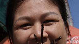 """Seorang pedagang Kamboja menunjukkan tarantula goreng yang dijualnya di wilayah Skun, Provinsi Kampong Cham, 4 Desember 2019. Daerah yang kerap dijuluki """"Spiderville"""" tersebut menjadi tempat menarik bagi para turis berburu aping, camilan tradisional dari tarantula ini. (TANG CHHIN Sothy / AFP)"""