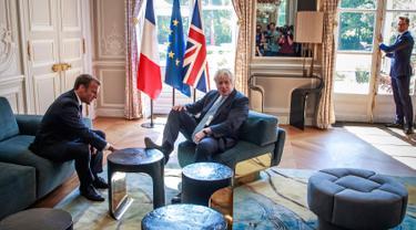 Perdana Menteri Inggris Boris Johnson menjadi sorotan setelah menaruh kaki di meja di depan Presiden Perancis Emmanuel Macron dalam kunjungan kenegaraan.(Christophe Petit Tesson, Pool via AP)