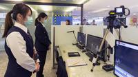 Personel Center for Disease Control (CDC) Taiwan memindai suhu tubuh penumpang yang tiba dari penerbangan Wuhan China di Bandara Taoyuan International (13/1/2020). Jumlah kematian yang diakibatkan oleh wabah virus corona hampir dua kali lipat hanya dalam 24 jam. (AFP Photo/Chen Chi-chuan)