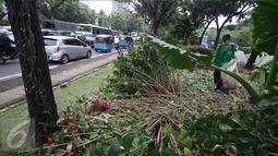 Pekerja membersihkan sampah berserakan di taman yang rusak di depan gedung Balai Kota Jakarta, Jumat (14/10). Taman tersebut rusak akibat banyaknya pengunjuk rasa yang menginjak-injak serta duduk di atas tanaman. Liputan6.com/Immanuel Antonius
