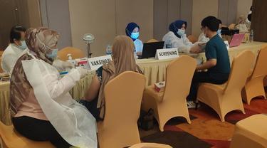 Pemberian vaksin Covid-19 kepada masyarakat di salah satu hotel di Pekanbaru.