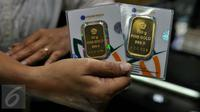 Pedagang menunjukan emas batangan 50 gram dan 100 gram di sebuah toko Kawasan Cikini, Jakarta, Kamis (3/9/2015). Harga emas milik PT Aneka Tambang Tbk (Antam) hari ini terpantau bergerak stabil di posisi Rp560 ribu per gram. (Liputan6.com/Johan Tallo)