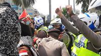 Aparat kepolisian mengamankan massa Aksi 1812 di kawasan Patung Kuda, Jakarta Pusat, Jumat (18/12/2020). Polisi mengimbau massa membubarkan diri dan kembali pulang. (Liputan6.com/Yopi Makdori)