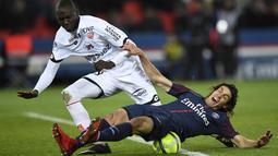 Pemain PSG, Edinson Cavani jatuh saat berebut bola dengan pemain Dijon, Cedric Yambere pada laga Ligue 1 di Parc des Princes stadium, Paris, (17/1/2018). PSG menang telak 8-0. (AFP/Christophe Simon)