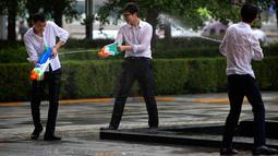 Tiga pekerja kantor bermain senjata air di luar gedung kantor, Beijing, (13/7). Karyawan di China terkadang menghabiskan waktu berjam-jam di tempat kerja dan beralih bermain dengan ide kreatif untuk menghilangkan stres. (AP Photo/Mark Schiefelbein)