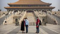 Pengunjung mengenakan masker saat berswafoto di Kota Terlarang, Beijing, China, Jumat (1/5/2020). Kota Terlarang kembali dibuka setelah ditutup lebih dari tiga bulan karena pandemi virus corona COVID-19. (AP Photo/Mark Schiefelbein)