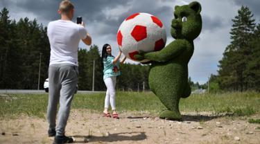Seorang wanita berpose di samping patung seekor anak beruang memegang bola yang terbuat dari dedaunan di dekat bandara Samara, Rusia (11/6). Rusia akan menjadi tuan rumah turnamen sepak bola Piala Dunia 2018. (AFP Photo/Fabrice Coffrini)