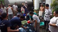 Gibran menyaksikan pemberian bantuan air bersih kepada warga di Kelurahan Kadipiro yang mengalami kekeringan, Jumat 91/11).(Liputan6.com/Fajar Abrori)