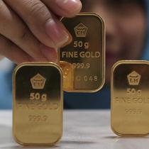 Petugas menunjukan emas batangan di kantor BNI Syariah, Jakarta, Senin (30/11). Harga jual-beli kembali (buyback) emas Antam turun Rp 1.000 usai akhir pekan kemarin naik di tengah turunnya harga emas global. (Liputan6.com/Angga Yuniar)