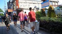 Turis mancanegara berjalan melewati papan izin mendirikan bangunan (biru) di bekas lokasi bom Bali Sari Club di Kuta, Bali, Jumat (26/4). Perdana Menteri Morrison kesal karena saat terjadi serangan Bom Bali pada 2002 di Sari Club, puluhan warga Australia tewas di tempat ini. (SONNY TUMBELAKA/AFP)