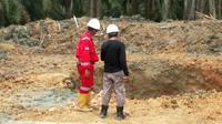Petugas mengecek lobang semburan gas di Pesantren Al Ihsan Pekanbaru. (Liputan6.com/M Syukur)