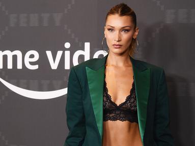 Model Bella Hadid berpose saat tiba menghadiri Savage X Fenty Show yang Disuguhkan oleh Amazon Prime Video di Brooklyn, New York (10/9/2019). Bella Hadid tampil seksi mengenakan bra renda dengan setelan jas hijau. (AFP Photo/Dimitrios Kambouris)