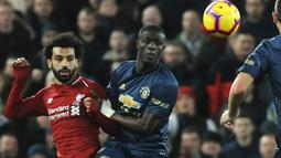 Striker Liverpool, Mohamed Salah berebut bola dengan pemain Manchester United, Eric Bailly dalam lanjutan pekan ke-17 Premier League di Stadion Anfield, Minggu (16/12). The Reds mengalahkan rival abadi, Manchester United dengan skor 3-1. (AP/Rui Vieira)
