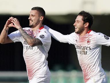 Pemain AC Milan, Rade Krunic, melakukan selebrasi bersama Davide Calabria usai mencetak gol ke gawang Verona pada laga Liga Italia di Stadion Bentegodi, Minggu (7/3/2021). AC Milan menang dengan skor 2-0. (Spada/LaPresse via AP)