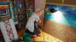 Seniman asal Ukraina, Dariya Marchenko saat menunjukkan karya seni peluru lainnya di Kiev, Ukraina (27/7/2015). Dariya mengungkapkan peluru memiliki arti tersembunyi dan kehidupan manusia berakhir dengan kebrutalan. (REUTERS/Gleb Garanich)