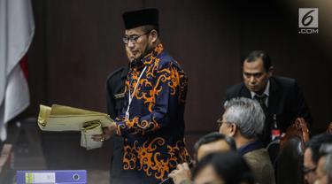 Komisioner KPU, Hasyim Asyari membawa amplop untuk ditunjukkan kehadapan Majelis Hakim dan tim kuasa hukum pasangan Prabowo Subianto-Sandiaga Uno dalam sidang lanjutan sengketa pilpres 2019 di Gedung Mahkamah Konstitusi (MK), Jakarta, Kamis (20/6/2019). (Liputan6.com/Faizal Fanani)
