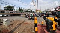 Sejumlah kendaraan berhenti di perlintasan kereta api Nomor 52 di Pisangan Lama, Jakarta, Kamis (11/4). Pintu perlintasan ini dan JPL 66 di Jalan Stasiun Cakung, Jaktim, akan ditutup permanen saat diberlakukannya Double Double Track (DDT) lintas Manggarai-Cikarang. (merdeka.com/Iqbal S. Nugroho)