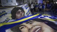Para penggemar mantan bintang sepak bola Argentina, Diego Maradona berkumpul di luar rumah sakit tempatnya akan menjalani operasi di Olivos, Buenos Aires, Selasa (3/11/2020). Diego Maradona menjalani operasi hematoma subdural atau pembekuan darah di otak. (JUAN MABROMATA / AFP)