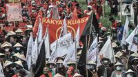Massa buruh dan tani saat menggelar longmarch menuju Istana Negara di Jalan Salemba Raya, Jakarta, Selasa (20/10/2020). Mereka juga mendesak Presiden Joko Widodo segera menerbitkan Perppu pembatalan UU Cilaka. (merdeka.com/Iqbal S. Nugroho)