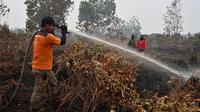 Prajurit TNI dan petugas Badan Penanggulangan Bencana Daerah (BPBD) berusaha memadamkan kebakaran hutan dan lahan di Kabupaten Kampar, Provinsi Riau (12/9/2019). Kebakaran hutan yang terjadi menyebarkan kabut asap di Asia Tenggara. (AFP Photo/Adek Berry)
