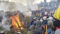 Demonstran membakar pohon di luar gedung parlemen di Quito (8/10/2019). Unjuk rasa ini telah berlangsung selama beberapa hari dan diikuti berbagai elemen termasuk masyarakat adat. (AFP Photo/Martin Bernetti)