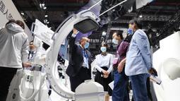 Seorang staf (keempat dari kanan) memperkenalkan sebuah mesin sinar X kepada para pengunjung dalam acara Pameran Alat Medis Internasional China (China International Medical Equipment Fair) di Shanghai, China, 19 Oktober 2020. (Xinhua/Fang Zhe)