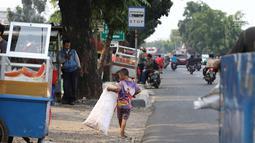 Seorang anak memungut sampah plastik di Jakarta, Rabu (12/9). Target bebas pekerja anak pada tahun 2022 disampaikan delegasi Indonesia dalam pertemuan anggota organisasi buruh internasional (ILO) di Jenewa, Swiss. (Liputan6.com/Immanuel Antonius)