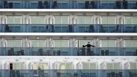 Penumpang berdiri di balkon kapal pesiar Diamond Princess di Daikoku Pier Cruise Terminal di Yokohama (7/2/2020). Ribuan penumpang terpaksa harus dikarantina setelah seorang penumpang yang turun di Hong Kong pada Januari lalu dinyatakan positif terinfeksi Corona. (AP Photo/Eugene Hoshiko)