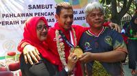 Pesilat peraih medali emas Asian Games 2018, Hanifan Yudani Kusumah, diapit kedua orang tua. (Bola.com/Erwin Snaz)