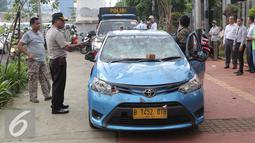 Petugas mengamankan mobil taksi yang hancur akibat dirusak oleh ojek online di Jakarta, Selasa (22/3). Akibat aksi saling serang antara taksi dan ojek online berimbas pada kerusuhan yang terjadi di beberapa titik di Jakarta. (Liputan6.com/Angga Yuniar)