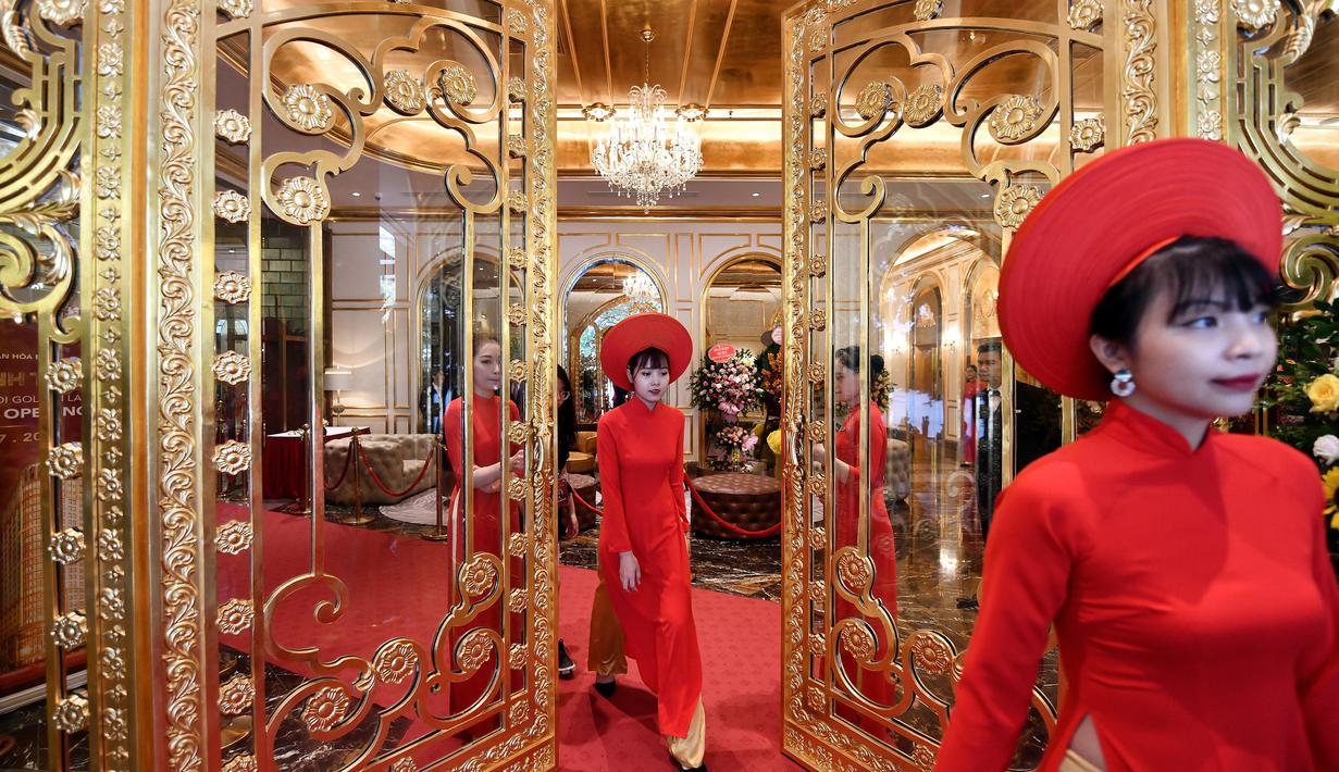 Pegawai bersiap untuk menyambut para tamu di lobi hotel Dolce Hanoi Golden Lake yang baru saja diresmikan di Hanoi, Vietnam pada Kamis (2/7/2020). Hotel tersebut merupakan hotel berlapiskan emas 24 karat pertama di dunia. (Manan VATSYAYANA / AFP)