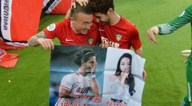 Penyerang Tianjin Quanjian, Alexandre Pato dan rekannya membawa poster aktris Dilraba Dilmurat usai pertandingan melawan South Hyundai Jeonbuk di Liga Champions AFC  di Tianjin (14/3). Poster tersebut tidak diketahui siapa yang buat. (AFP Photo)