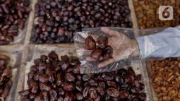 Pedagang menunjukkan kurma dagangannya di Pasar Tanah Abang, Jakarta, Rabu (22/4/2020). Pandemi COVID-19 membuat lesu penjualan kurma, keuntungan pedagang menurun hingga 80 persen lebih padahal pada tahun sebelumnya menjelang Ramadan biasanya ramai pembeli. (Liputan6.com/Johan Tallo)